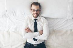 Взгляд сверху Красивый бизнесмен при стекла лежа на кровати стоковое изображение