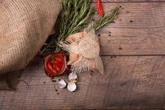 Взгляд сверху красного пряного перца chili в стеклянном опарнике, раковины яичек триперсток и хворостины розмаринового масла на д Стоковое фото RF
