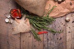 Взгляд сверху красного пряного перца chili в стеклянном опарнике, хворостин greeen rosematy, раковина яичек триперсток на деревян Стоковое Фото
