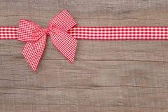 Взгляд сверху красного цвета проверило украшение ленты на деревянной предпосылке Стоковая Фотография RF