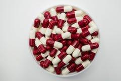 Взгляд сверху красной, белое, пилюльки капсулы в пластмасовом контейнере Стоковые Изображения RF