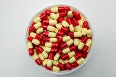 Взгляд сверху красной, палевое, пилюльки капсулы в пластмасовом контейнере Стоковое фото RF