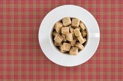 Взгляд сверху кубов желтого сахарного песка белого кофе или чашки чая полных на красной приданной квадратную форму предпосылке На Стоковые Фотографии RF