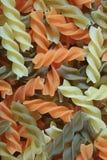 Взгляд сверху макаронных изделий сырой спирали 3-цвета форменных, Tricolor Fusilli, для предпосылки стоковая фотография