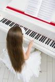 Взгляд сверху маленького ребенка в белом платье играя рояль стоковое изображение