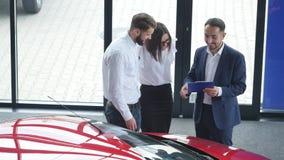 Взгляд сверху молодого мужских консультанта и покупателей подписывая контракт для нового автомобиля в автосалоне Концепция для пр сток-видео