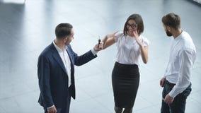 Взгляд сверху молодого мужских консультанта и покупателей подписывая контракт для нового автомобиля в автосалоне Концепция для пр видеоматериал