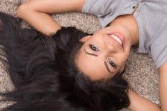 Взгляд сверху молодой женщины лежа на ковре стоковое изображение rf
