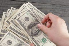 Взгляд сверху молодых женских долларовых банкнот отсчета рук Стоковое фото RF