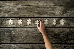 Взгляд сверху мужской руки устанавливая 7 пустых частей головоломки в ряд Стоковое Фото