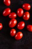 Взгляд сверху на нескольких красных томатов вишни на черной доске Стоковое Изображение