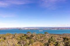 Взгляд сверху на Окленде и заливе Hauraki при контейнеровоз проходя мимо Стоковая Фотография RF