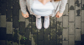 Взгляд сверху ног женщины в белых тапках outdoors Стоковое Изображение RF