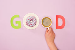 Взгляд сверху доброго слова сделанное от и чашки кофе в человеческих руке и donuts Стоковые Изображения