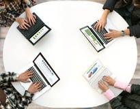 Взгляд сверху округленного стола при 4 компьтер-книжки и руки людей печатая на клавиатуре Стоковые Фотографии RF