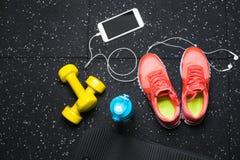 Взгляд сверху оранжевых ботинок спорта, желтых гантелей, циновки pilates, голубой бутылки, и телефона с наушниками на черноте Стоковое Изображение RF