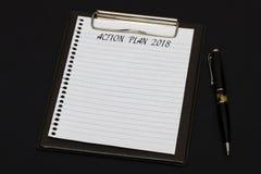 Взгляд сверху доски сзажимом для бумаги и белого листа написанных с ПЛАНОМ ДЕЙСТВИЯ 2 Стоковое фото RF