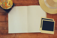 Взгляд сверху открытой пустой тетради и и пустых поляроидных рамок фотографии рядом с старыми глобусами над деревянным столом под Стоковая Фотография RF