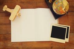 Взгляд сверху открытой пустой тетради и и пустых поляроидных рамок фотографии рядом с старыми глобусами над деревянным столом под Стоковое фото RF