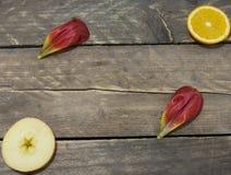 Взгляд сверху Отрезанные апельсин и яблоко с лист тюльпана на деревянные животики Стоковое Фото