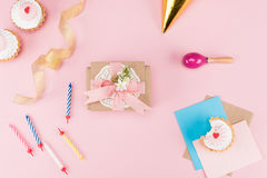 Взгляд сверху очень вкусных пирожных, красочных свечей и декоративного конверта на пинке Стоковая Фотография RF