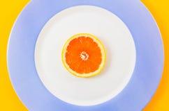 Взгляд сверху одиночного куска грейпфрута на централизованно помещенной плите Стоковые Фото