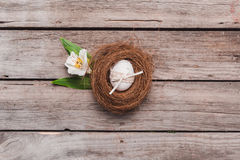 Взгляд сверху пасхального яйца с лентой в гнезде с цветком на деревянной столешнице Стоковая Фотография RF