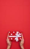 Взгляд сверху подарка в женских руках над красной квартирой кладет предпосылку Стоковая Фотография RF