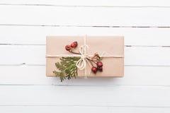 Взгляд сверху подарка рождества обернутое в ремесле и украшенное с различными естественными вещами на белой древесине Стоковые Фото