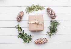 Взгляд сверху подарка рождества обернутое в ремесле и украшенное с различными естественными вещами на белой древесине Стоковые Изображения RF