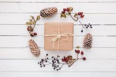 Взгляд сверху подарка рождества обернутое в ремесле и украшенное с различными естественными вещами на белой древесине Стоковое фото RF