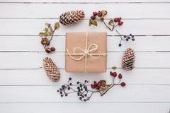 Взгляд сверху подарка рождества обернутое в ремесле и украшенное с различными естественными вещами на белой древесине Стоковое Изображение