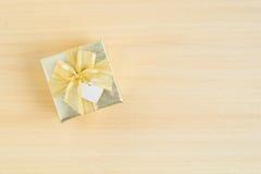 Взгляд сверху подарочной коробки золота на деревянной предпосылке Стоковое Фото