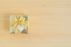 Взгляд сверху подарочной коробки золота на деревянной предпосылке Стоковая Фотография