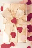 Взгляд сверху подарочной коробки золота с красным цветом и разбросанными пинком сердцами Стоковые Изображения RF