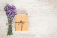 Взгляд сверху подарочной коробки обернутой в букете бумаги и лаванды kraft над белой деревянной деревенской предпосылкой скопируй Стоковая Фотография RF