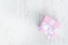 Взгляд сверху подарочной коробки обернутой в пинке поставило точки бумага и связало смычок сатинировки над белой деревянной предп Стоковые Изображения RF