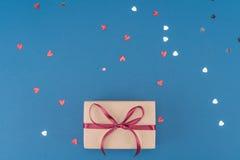 Взгляд сверху подарочной коробки, сердца сформировало confetti на сини Стоковые Изображения RF