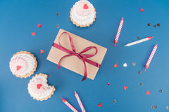Взгляд сверху подарочной коробки, тортов и свечей изолированных на сини Стоковые Фотографии RF