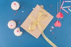 Взгляд сверху подарочной коробки, тортов и свечей на сини Стоковые Фото