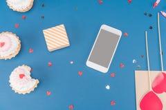 Взгляд сверху подарочной коробки, smartphone и тортов на сини Стоковое Изображение
