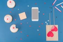 Взгляд сверху подарочной коробки, smartphone, тортов и свечей на сини Стоковое Фото