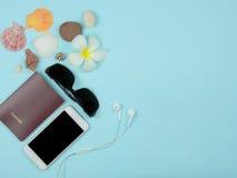 Взгляд сверху предпосылки путешественника, smartphone, пасспорта, солнечных очков, шлемофона телефона, с космосом экземпляра Стоковое фото RF