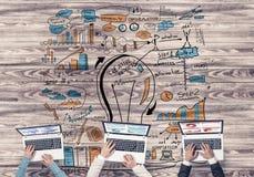 Взгляд сверху предпринимателей сидя на таблице и используя устройства Стоковое фото RF