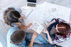 Взгляд сверху профессиональных молодых архитекторов работая совместно Стоковое Фото