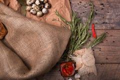 Взгляд сверху пряного перца chili в опарнике, розмаринового масла, spekled яичка триперсток, бумага бакалеи на деревянной предпос Стоковое Изображение RF