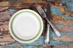 Взгляд сверху пустых плиты и столового прибора года сбора винограда на деревянной доске Стоковые Фотографии RF