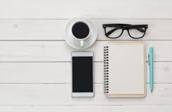 Взгляд сверху пустых тетради, мобильного телефона и чашки кофе Стоковое фото RF