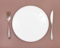 Взгляд сверху плиты фарфора, вилки, ножа на коричневом цвете Стоковое Изображение RF