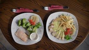 Взгляд сверху плит с едой от ресторана, которые стоят на деревянном столе На блюдах лежит рыба с акции видеоматериалы